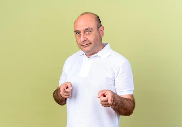 올리브 녹색 벽에 고립 된 제스처를 보여주는 기쁘게 성숙한 남자