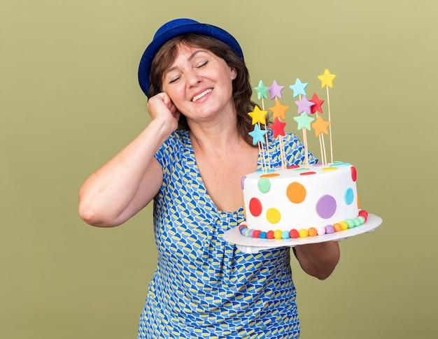 Piacevole donna di mezza età con cappello da festa che tiene in mano una torta di compleanno sorridendo allegramente