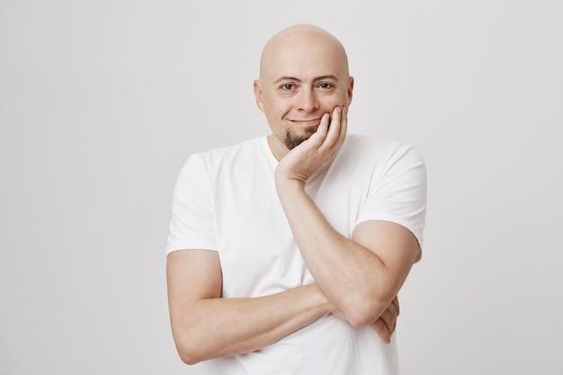 Pleased middle-aged bald man looking with satisfaction, smiling
