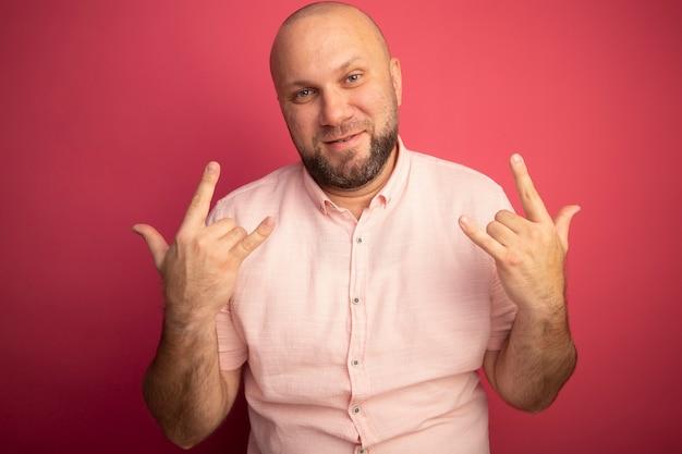 Uomo calvo di mezza età soddisfatto che indossa la maglietta rosa che mostra il gesto della capra isolato sul colore rosa