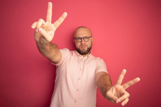 분홍색에 고립 된 평화 제스처를 보여주는 안경 분홍색 티셔츠를 입고 기쁘게 중년 대머리 남자