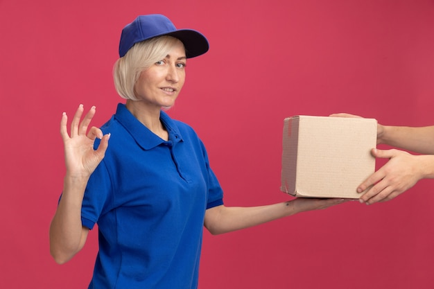 Pleased middle-aged blonde delivery woman in blue uniform and cap giving cardboard box to client doing ok sign