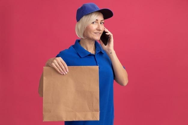 Lieta donna di mezza età bionda consegna in uniforme blu e berretto parlando al telefono tenendo il pacchetto di carta guardando la parte anteriore isolata sulla parete rosa con spazio di copia
