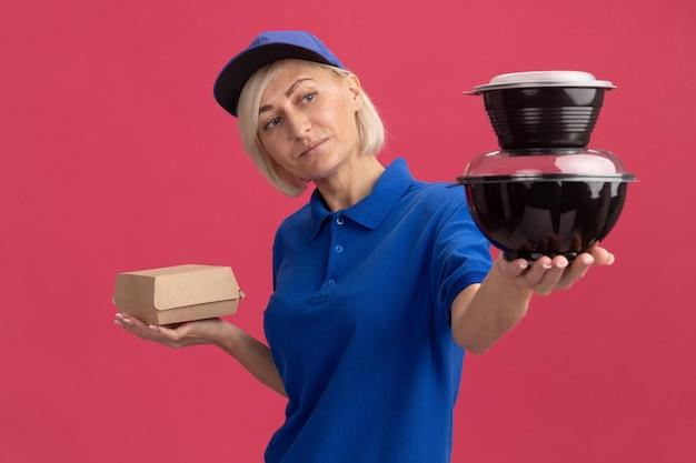 파란색 유니폼을 입은 행복한 중년 금발 배달부와 종이 음식 패키지를 들고 있는 모자를 들고 분홍색 벽에 격리된 음식 용기를 정면으로 바라보고 있습니다.