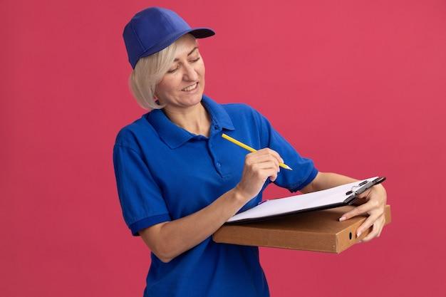 Довольная блондинка среднего возраста доставщица в синей форме и кепке держит пакет пиццы с карандашом и буфером обмена, глядя в буфер обмена