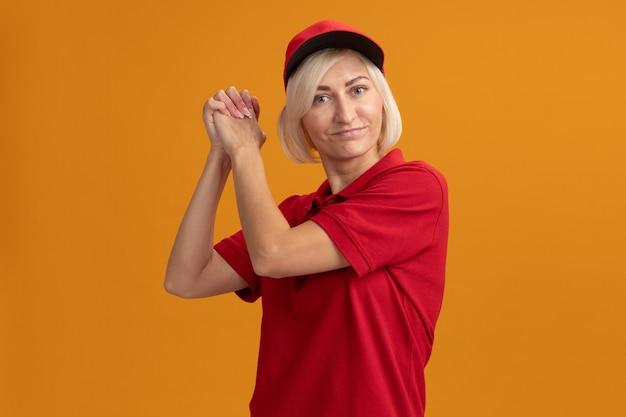 빨간 제복을 입은 행복한 중년 금발 배달부와 모자를 쓰고 앞을 바라보는 모자는 카피 공간이 있는 주황색 벽에 격리된 승리의 제스처를 보여줍니다
