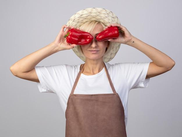 白い壁に隔離された目の前に唐辛子を保持している帽子をかぶって制服を着た中年の金髪の庭師の女性を喜ばせる