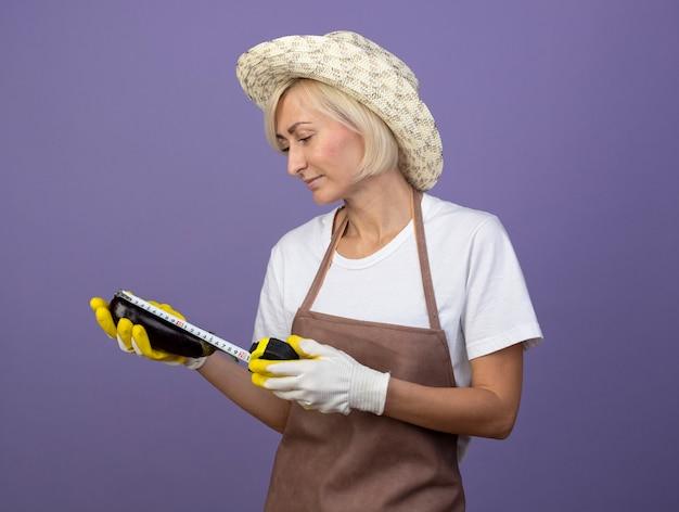 Lieta mezza età giardiniere bionda donna in uniforme che indossa un cappello e guanti da giardinaggio guardando e misurando la melanzana con metro a nastro