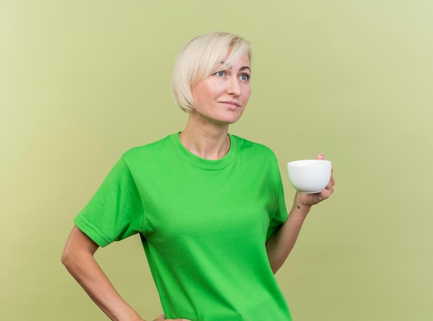 Pleased middle-aged blonde slavic woman holding cup of tea keeping hand on waist looking straight isolated on olive green wall with copy space