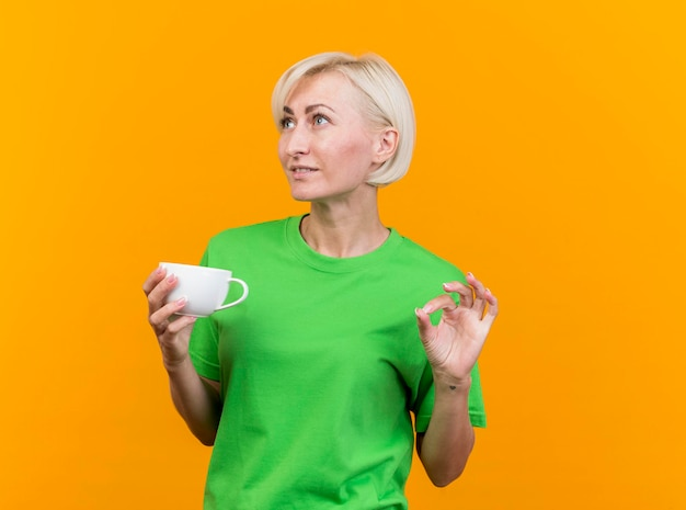 Pleased middle-aged blonde slavic woman holding cup of tea looking at side doing ok sign isolated on yellow wall with copy space