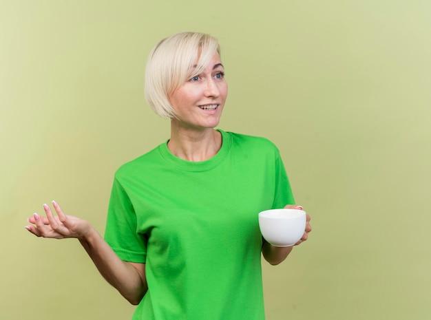 Felice donna slava bionda di mezza età tenendo la tazza di tè guardando il lato che mostra la mano vuota isolata sulla parete verde oliva con lo spazio della copia