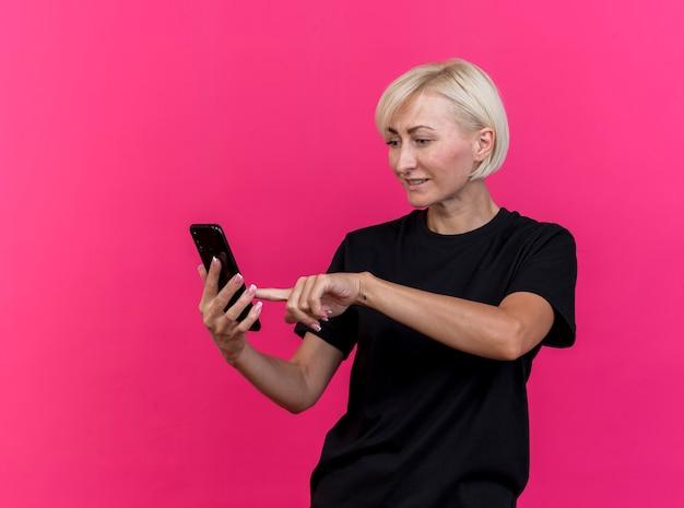 コピースペースのある深紅色の壁に隔離された携帯電話を使用して携帯電話を見て保持している中年の金髪のスラブ女性を喜ばせる