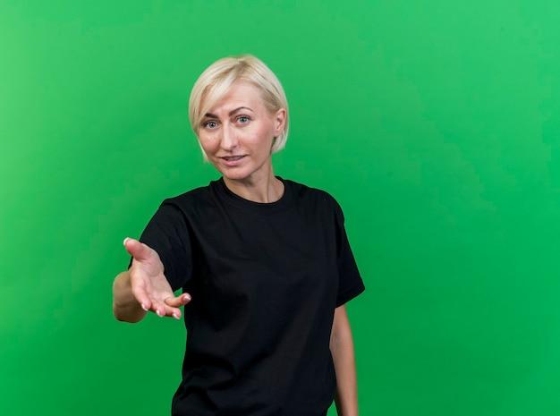 Довольная блондинка средних лет славянская женщина смотрит в камеру, протягивая руку к камере, изолированной на зеленом фоне с копией пространства