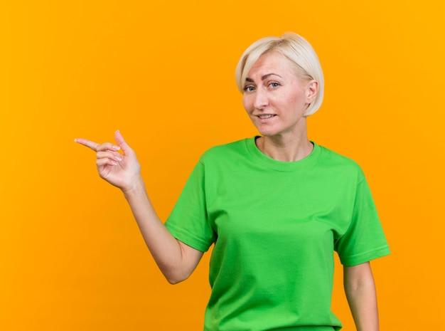 黄色の壁に隔離された側を指している正面を見て喜んで中年の金髪のスラブ女性