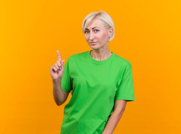 Довольная белокурая славянская женщина средних лет смотрит вперед, указывая вверх, изолированную на желтой стене с копией пространства