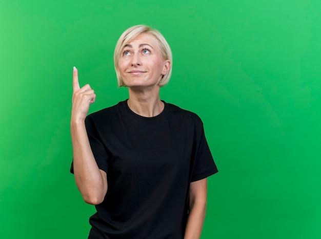 Donna slava bionda di mezza età soddisfatta che osserva e che indica in su isolato su priorità bassa verde con lo spazio della copia