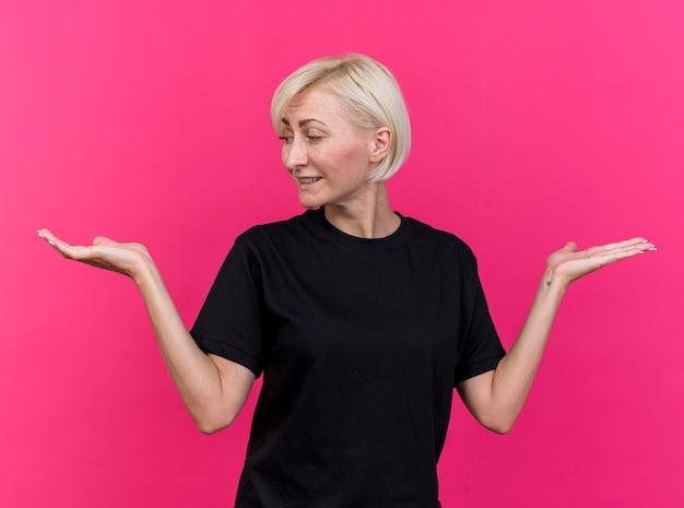 Donna slava bionda di mezza età soddisfatta che mostra le mani vuote guardando uno di loro isolato sul muro rosa