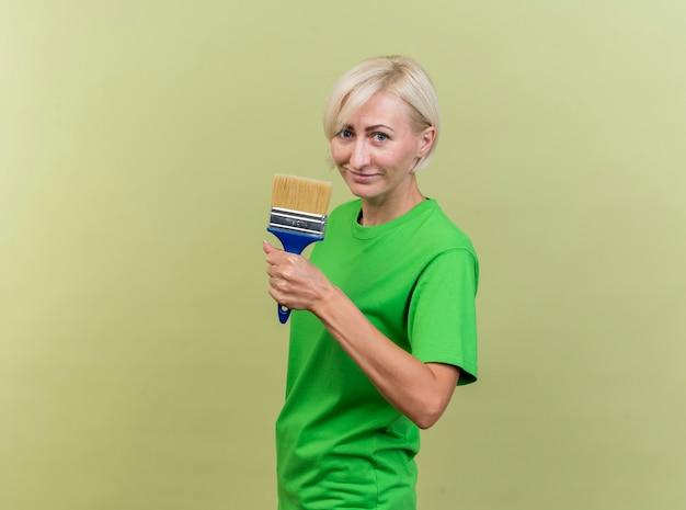 복사 공간 올리브 녹색 벽에 고립 된 페인트 브러시를 들고 프로필보기에 서 기쁘게 중년 금발 슬라브 여자