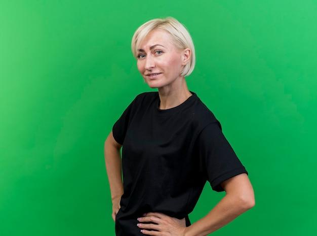 コピースペースで緑の背景に分離されたカメラを見て腰に手を保ちながら縦断ビューで立っている満足している中年の金髪のスラブ女性