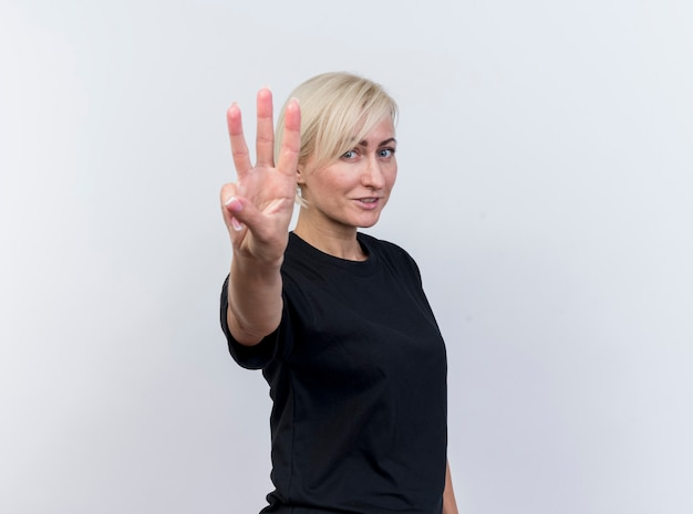 복사 공간 흰색 배경에 고립 된 손으로 세를 보여주는 카메라를보고 프로필보기에 서 기쁘게 중년 금발 슬라브 여자