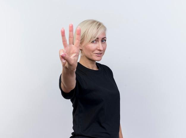 Lieta di mezza età bionda donna slava in piedi in vista di profilo guardando la telecamera che mostra tre con mano isolati su sfondo bianco con spazio di copia