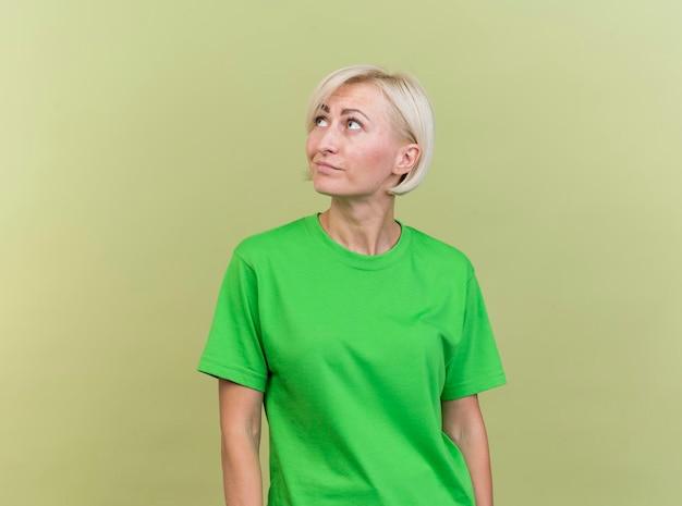 기쁘게 중년 금발 슬라브 여자 복사 공간 올리브 녹색 벽에 고립 된 찾고 머리를 측면