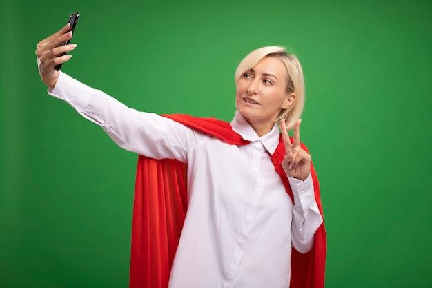 Donna bionda di mezza età felice del supereroe in mantello rosso che fa il segno di pace che prende selfie isolato sulla parete verde con lo spazio della copia