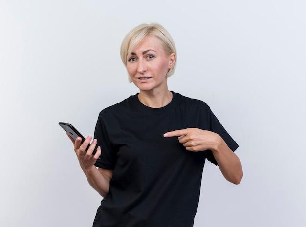 Lieta donna bionda di mezza età guardando la tenuta anteriore e indicando il telefono cellulare isolato sul muro bianco