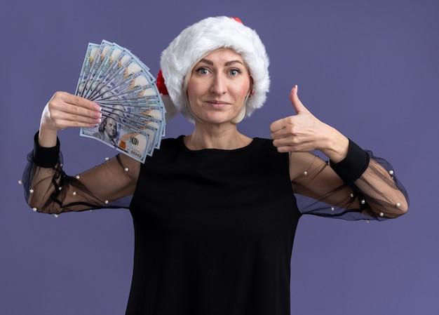 보라색 배경에 고립 엄지 손가락을 보여주는 카메라를보고 돈을 들고 크리스마스 모자를 쓰고 기쁘게 중년 금발의 여자