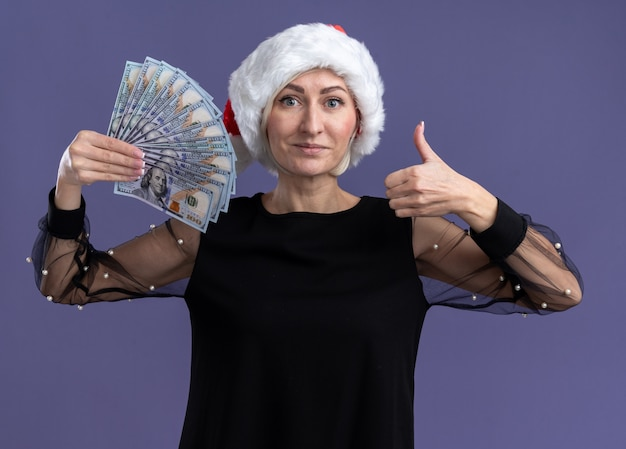 Pleased middle-aged blonde woman wearing christmas hat holding money looking at camera showing thumb up isolated on purple background