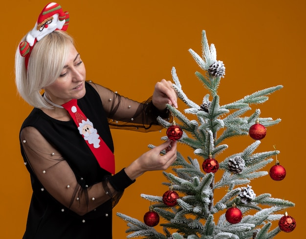 Pleased middle-aged blonde woman wearing santa claus headband and tie standing in profile view near christmas tree looking at it and decorating it with christmas decoration balls isolated on orange wall
