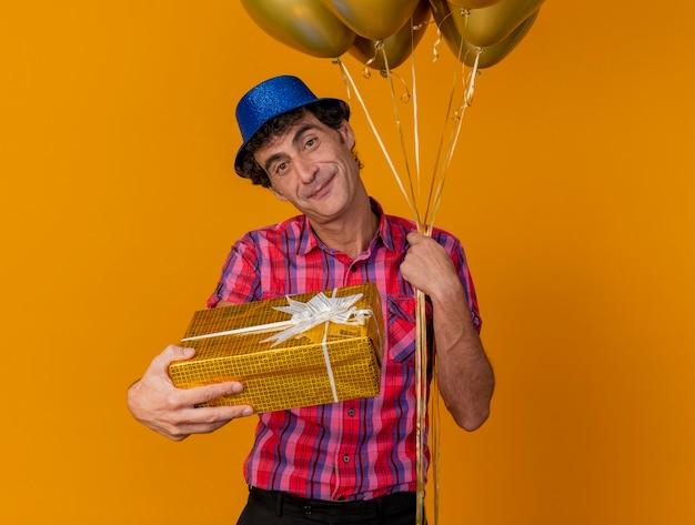 복사 공간 오렌지 배경에 고립 된 카메라를 향해 선물 팩을 뻗어 카메라를보고 풍선을 들고 파티 모자를 쓰고 기쁘게 중년 백인 파티 남자