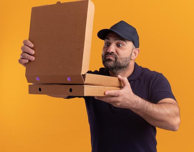 Uomo di consegna di mezza età soddisfatto in uniforme e cappuccio che apre e annusa le scatole della pizza isolate sulla parete gialla