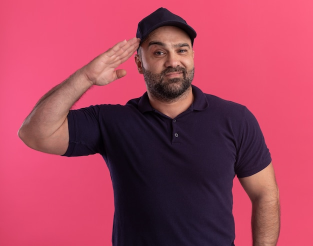 Pleased middle-aged delivery man in uniform and cap showing salute gesture isolated on pink wall