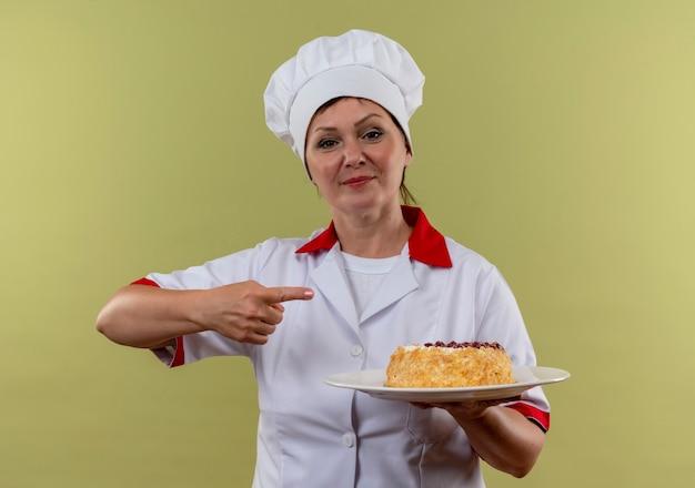 Piacevole cuoca di mezza età in uniforme da chef tenendo la torta sul piatto e punta il dito a lato sulla parete verde isolata con lo spazio della copia