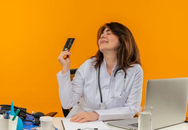 의료 가운과 청진기를 착용하고 의료 도구 클립 보드와 노트북이 고립 된 닫힌 눈을 가진 신용 카드를 들고 책상에 앉아 기쁘게 중년 여성 의사