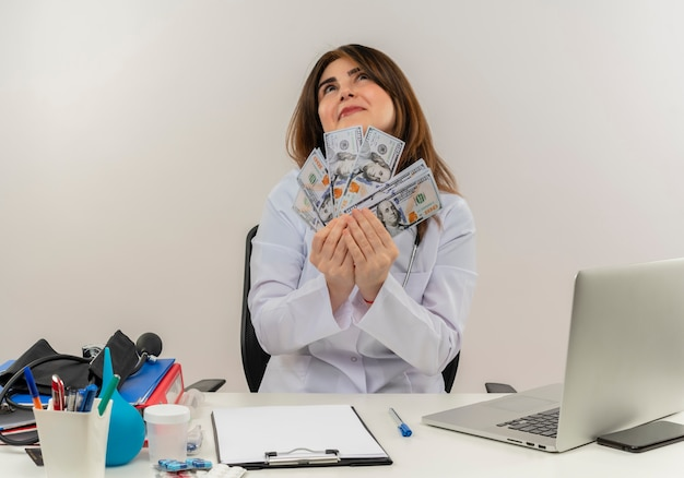 Felice donna di mezza età medico indossando abito medico e stetoscopio seduto alla scrivania con strumenti medici negli appunti e laptop tenendo i soldi cercando isolato