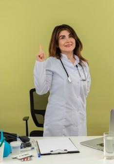 聴診器が机の後ろに立っている医療用ローブを身に着けている満足している中年の女性医師は、コピースペースのある孤立した緑の壁を指しています。