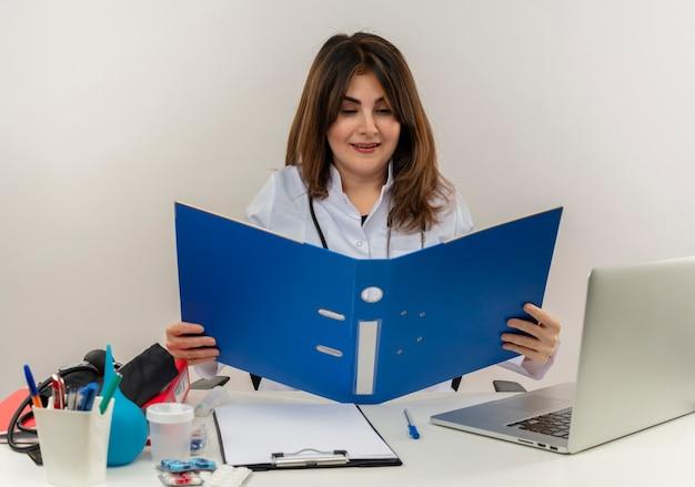Довольная женщина-врач средних лет в медицинском халате со стетоскопом сидит за столом и работает на ноутбуке с медицинскими инструментами, держа и глядя на папку на белой стене