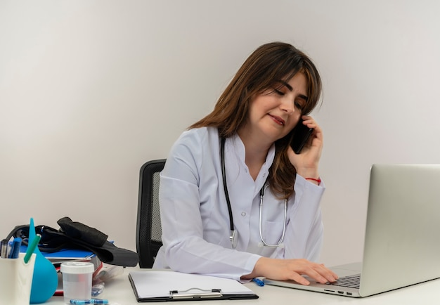 Pleased middle-aged female doctor wearing wearing medical robe with stethoscope sitting at desk work on laptop with medical tools speaks on phone and used laptop on white wall