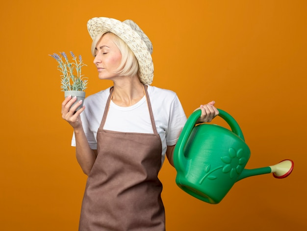 Felice giardiniere di mezza età donna in uniforme da giardiniere che indossa cappello tenendo annaffiatoio e vaso di fiori annusando fiori con gli occhi chiusi isolati sulla parete arancione