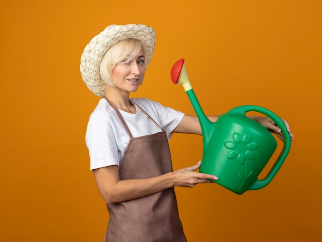 Pleased middle-aged gardener woman in gardener uniform wearing hat standing in profile view holding watering can  isolated on orange wall with copy space