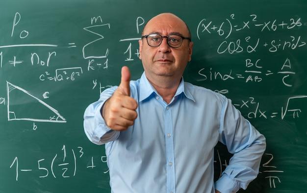 Compiaciuto insegnante maschio di mezza età con gli occhiali in piedi davanti alla lavagna che mostra il pollice in su