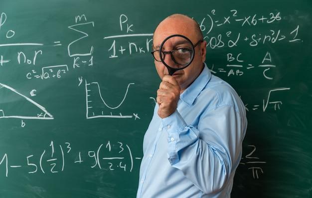 돋보기로 카메라를 찾고 칠판 앞에 서 안경을 쓰고 기쁘게 중년 남성 교사