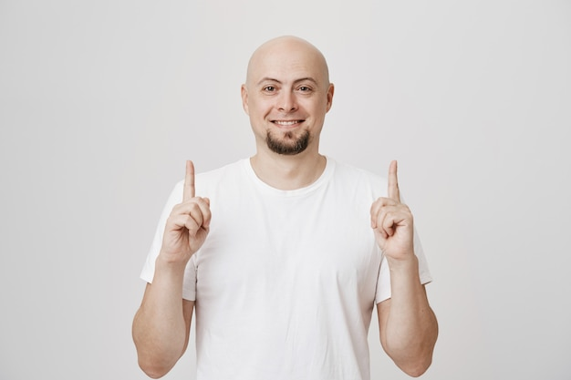Pleased middle-aged man smiling, pointing fingers up