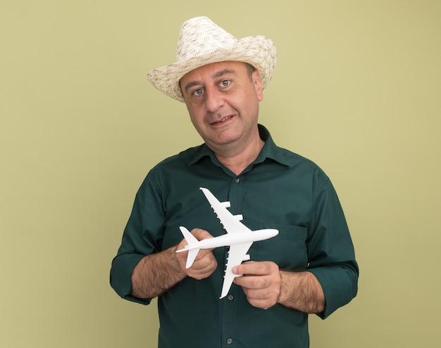 緑のtシャツとオリーブグリーンの壁に分離されたおもちゃの飛行機を保持している帽子を身に着けている中年男性