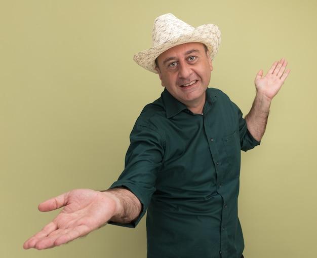 緑のtシャツとオリーブグリーンの壁に分離された手を広げる帽子を身に着けている中年男性を喜ばせる