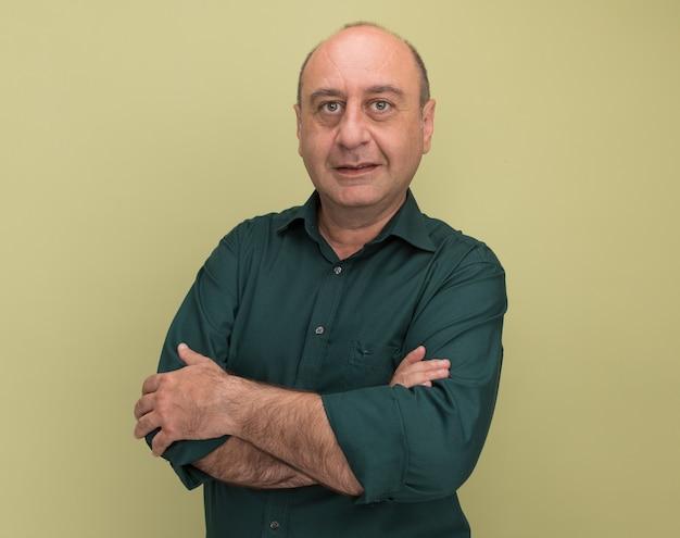 Довольный мужчина средних лет в зеленой футболке, скрестив руки, изолирован на оливково-зеленой стене