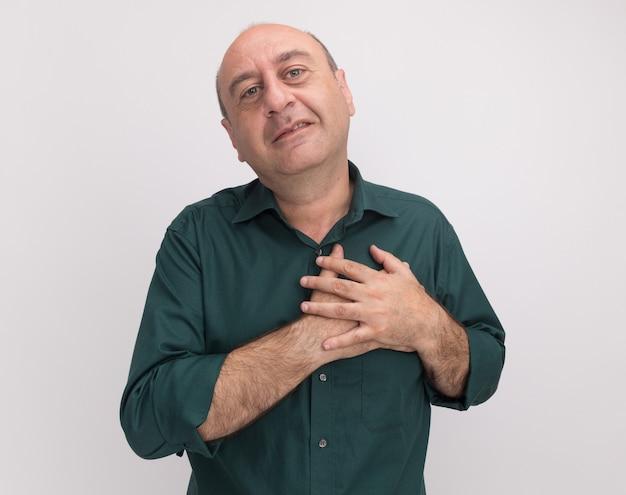 Felice uomo di mezza età che indossa la maglietta verde mettendo la mano sul cuore isolato sul muro bianco