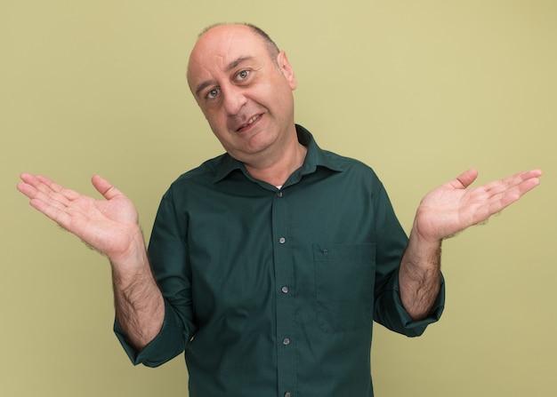 オリーブグリーンの壁に分離された手を広げて緑のtシャツを着て満足中年男性